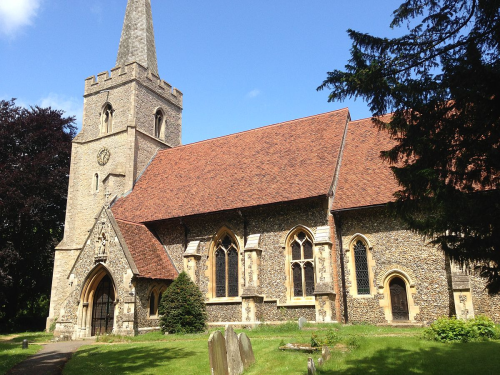 A church with a stone spire on a tower with a crenellated top, red-tiled roof, and wooden doors and glass-stained windows in pointed arches, with a churchyard in front of it.