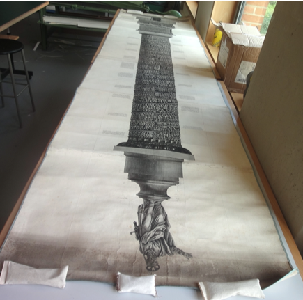 The full Colonna Trojana scroll laid out in the BLCC and held flat with weights