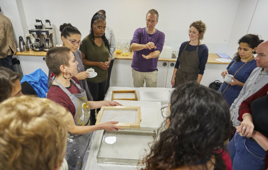 Delivery of the paper-making workshop at the BLQFP away day. The group stand around a desk watching demonstrations of mould and deckle paper-making tools.