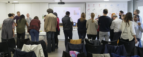 Workshops underway. An image from the back of the room showing the workshop participants engaged in listening to explanations and watching demonstrations on various desks laid out in the room.