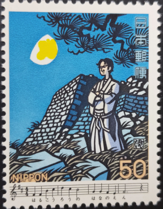 Stamp depicting a man standing in front of a ruined castle under moonlight with excerpts of the lyrics and score for the song Kōjō no tsuki