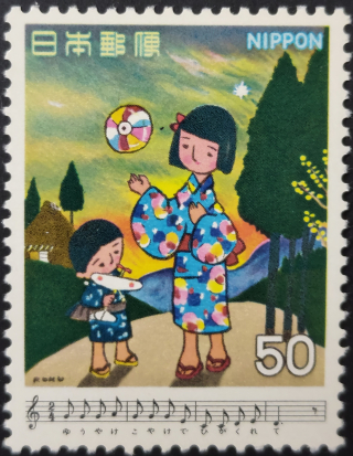 Stamp depicting a sunset scene with a boy holding a toy aeroplane beside a girl throwing a ball in the air along with an extract from the score and lyrics for the song Yūyake Koyake