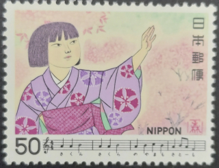 Stamp depicting a young Japanese girl reaching out towards cherry blossom with score and lyrics from the Edo Period song Sakura