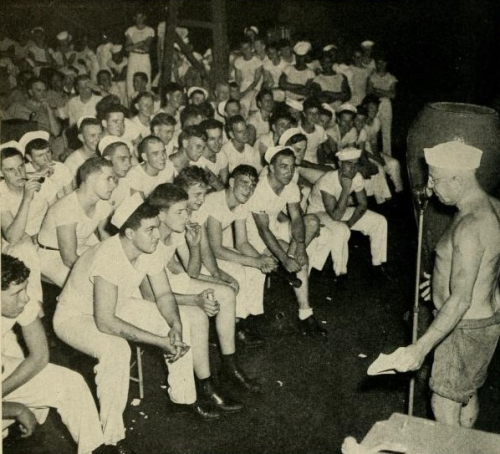 Rows of men sitting together as a crowd, wearing white sailor uniforms, some with hats. To the right, a man wearing a white hat and swimming trunks stands at a microphone, addressing them.