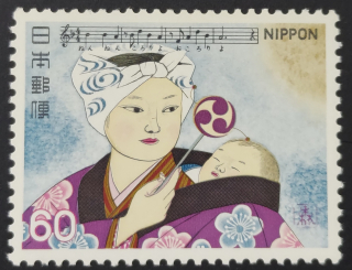 Stamp depicting a mother holding a baby whilst playing a Japanese drum called a den-den daiko with music to the song Komoriuta above it
