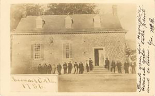 A sepia photograph of a tavern with 15 or so people standing in front.