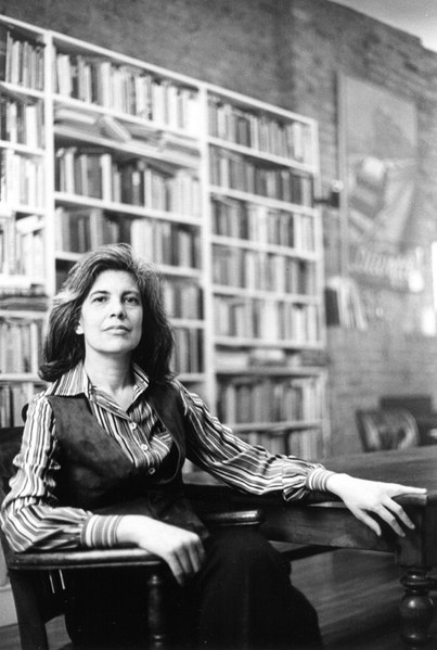 A photo of Susan Sontag sitting in her own home. Her left arm rests on a table and the right rests on the arm of the chair. Her dark hair is loose. She is wearing an open-necked striped shirt and a dark waistcoat. There are floor to ceiling bookcases in the background.