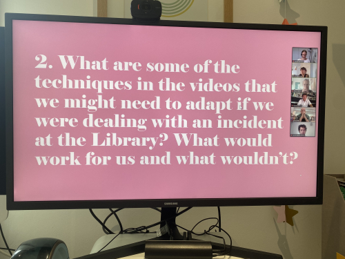 A computer monitor displaying a slide which says, 'What are some of the techniques in the videos that we might need to adapt if we were dealing with an incident at the Library? what would work for us and what wouldn't?' The text is white on a pink background and to the right of the monitor is a panel of participants in the Zoom meeting.