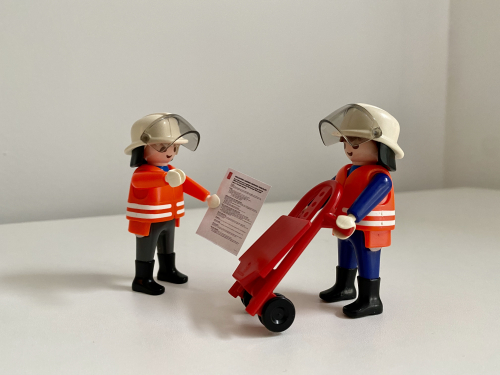 Two Playmobil figures: one is pushing a trolley and the other holds BL-branded paperwork. They are set up to simulate a salvage scene.