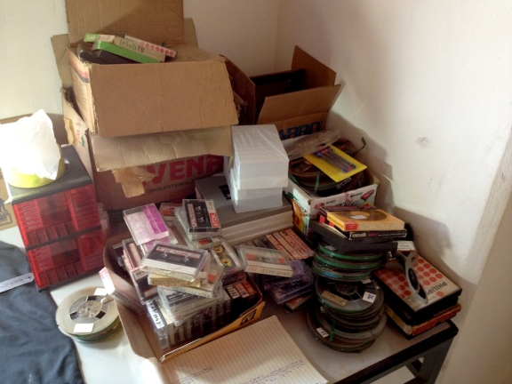 A slightly messy pile of cassettes and reels either loose or in cardboard boxes