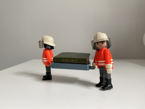Two ©Playmobil figures, wearing personal protective equipment, are shown carrying a miniature book between them.