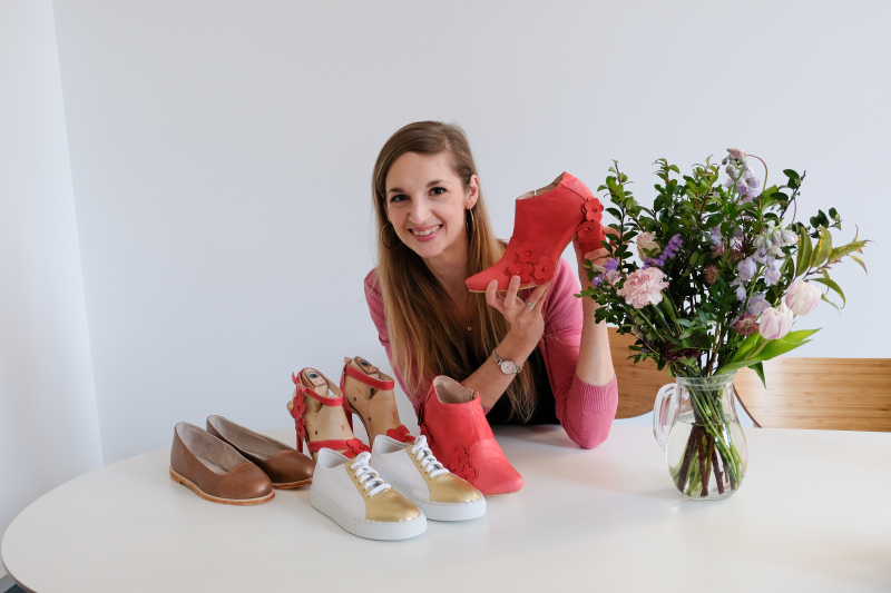 A woman holding shoes she's made with I Can Make Shoes