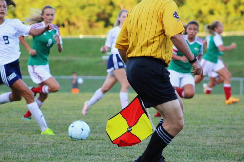 women playing soccer with a linesman in the foreground
