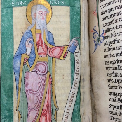 The left hand page of a highly pigmented illuminated manuscript. There is an illustration of a saint with a golden halo, wearing vibrant draping robes in a variety of pastel shades. There is a soft, pond green border.