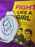 "A book called ""Fight like a Girl"" and an embroidered portrait of a woman."