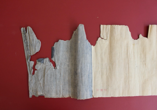 Verso before treatment showing a damaged and torn scroll laid out on a red table.