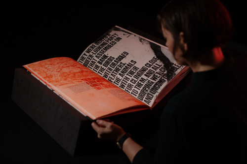 Image of a person holding open a large illustrated book