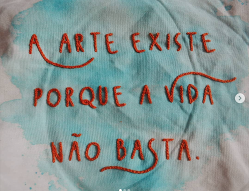 Image of a white canvas with light blue impressions and a phrase embroidered on it which reads: A arte existe porque a vida não basta/ Art exists because life is not enough
