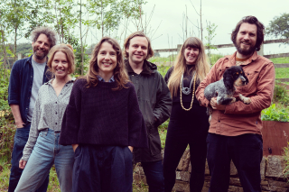 Group photograph of six people and a dog