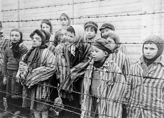 Black and white photo of child survivors of Auschwitz standing behind barbed wire