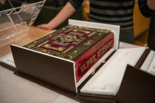 Photograph of the Lindisfarne Gospels being removed from its box for display in the Anglo-Saxon Kingdoms exhibition