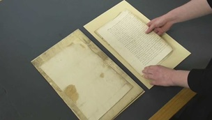 Image of archival material being carefully handled