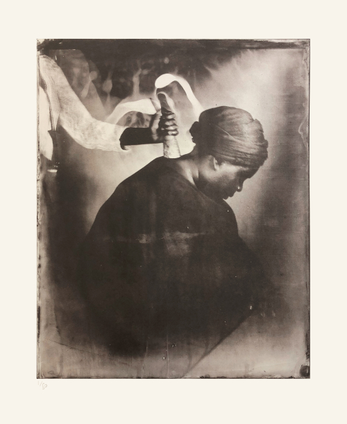 A person only partially visible places a cow horn on the back of Khadija Saye's neck