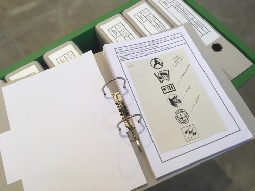 Two-ring binder open with black and white page of illustrations, atop a green open-topped box with obscured items