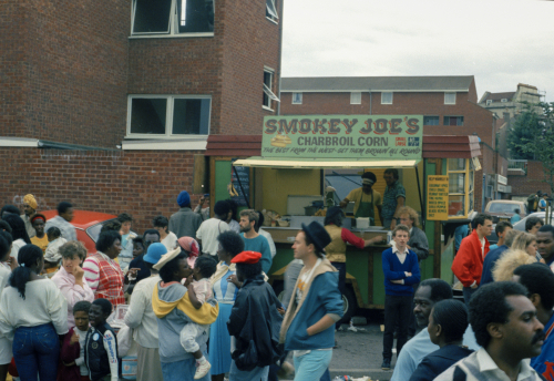 Photograph of a crowd of people on the street by a green food truck