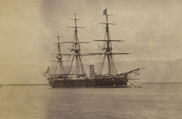 Photograph of starboard side of H.M.S Druid, a corvette at sea with sails down, 1880