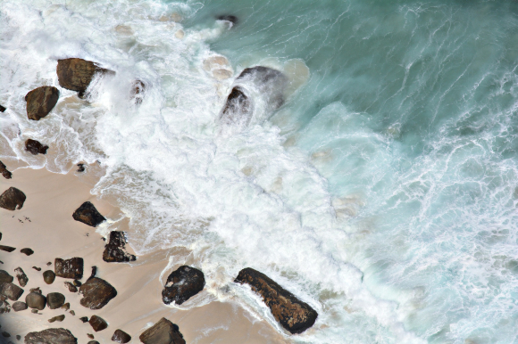 Waves breaking on a sandy beach with rocks