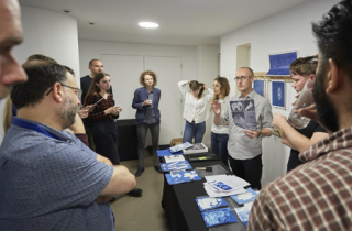 Cyanotype workshop in progress. The participants stand and listen to an explanation of the cyanotype method.