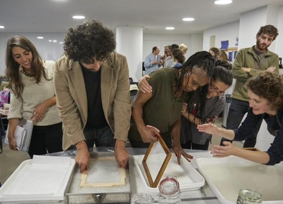Making papers and couching the sheets. The participants dip their paper moulds into a vat of paper pulp on the desk to make their paper sheets. They are helped by the tutor Camille.