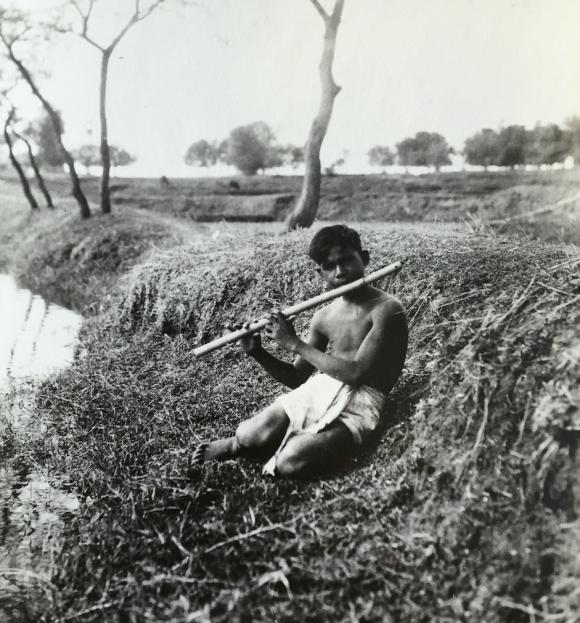 Santali flute player by pond