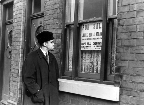 Black and white photograph of Malcolm X taking a walk down Marshall Street in Smethwick, to inspect the housing segregation practices supported by the Conservative-led Council