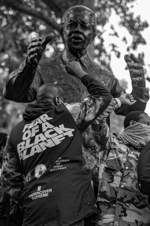 Black and white photographic image of a young man wearing a Public Enemy 'Fear of a Black Planet' jacket raises a Black Power fist by a statue of Nelson Mandela in Parliament Square, London, on 6 June 2020