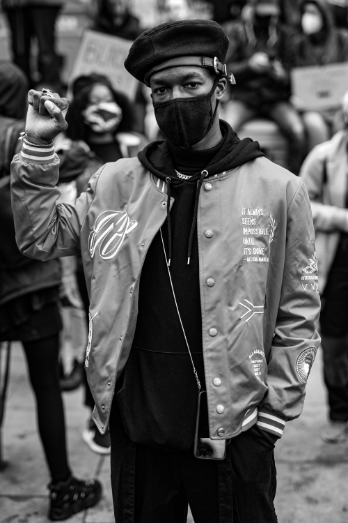 Black and white photographic image of a man wearing the black beret that was part of the US Black Panthers' 'uniform' while raising his fist. The embroidery on his jacket is a quotation by Nelson Mandela