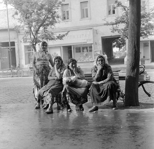 Photograph of four Romani women. Three are sitting on a bench and one is standing
