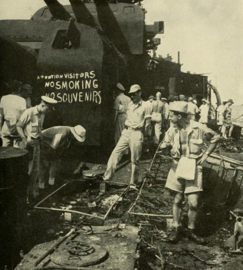 A group of sailors inspect the damage aboard a naval vessel, in front of a sign chalked onto the hull.