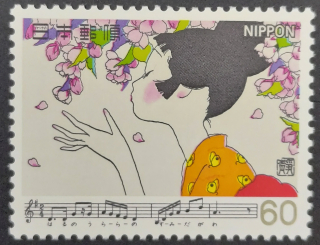Stamp depicting a woman smelling blossom upon a branch with music to Hana