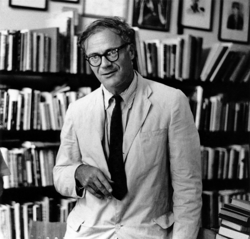 Robert Lowell stands in front of a wall of books, wearing a light jacket, dark tie, striped shirt and glasses.