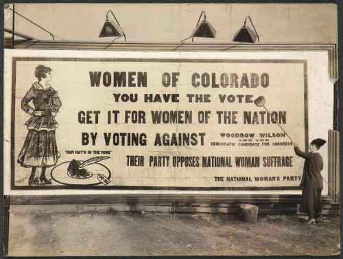 "Photograph of unidentified woman putting up billboard with bucket and broom. Billboard reads: ""'Women of Colorado, you have the vote. Get it for women of the nation by voting against Woodrow Wilson and the Democratic Candidate for Congress. Their party opposes national woman suffrage. The National Woman's Party."""