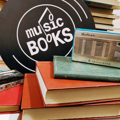 Pile of books with a transistor radio and sign reading 'music books'