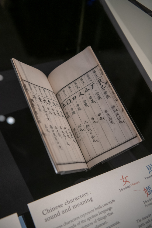 A book of Chinese characters open inside a display case
