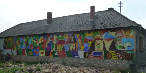 Mural on the side of a building by Rozi Csámpai depicting everyday life in Bódvalenke
