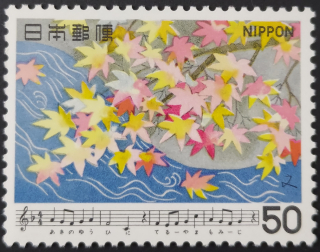 Stamp depicting yellowish-red maple leaves being blown off a tree branch beneath the music and lyrics of the song Momiji