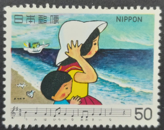 Stamp depicting a young Japanese boy and girl looking out to sea with a boat in the background and music and lyrics from the song Umi