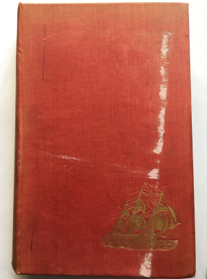 The picture of the front cover before conservation showing a red cover with a gold leaf ship in the lower right hand corner. Some loss is evident on the cover..