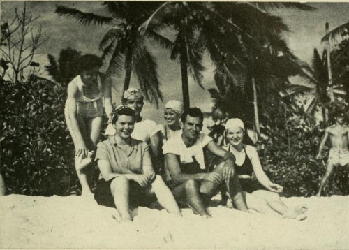 A group of women and men sitting together on a tropical beach, wearing beachwear, palm trees some distance behind, looking at the camera. There is also one man off to the right, standing, wearing swimming trunks.