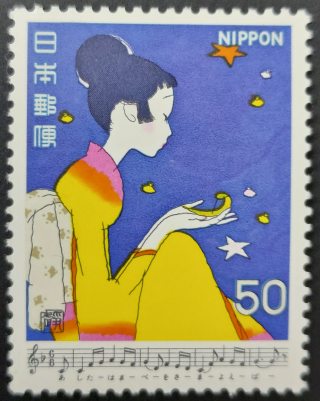 Stamp depicting a Japanese woman seated under a night sky with music for Hamabe no uta
